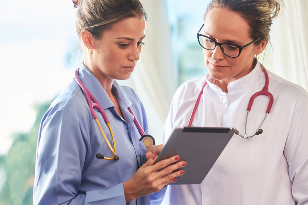 Image of a two nurses looking at a mobile electronic tablet