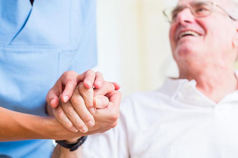 Close-up image of a FNP DNP nurse holding a patient's hand
