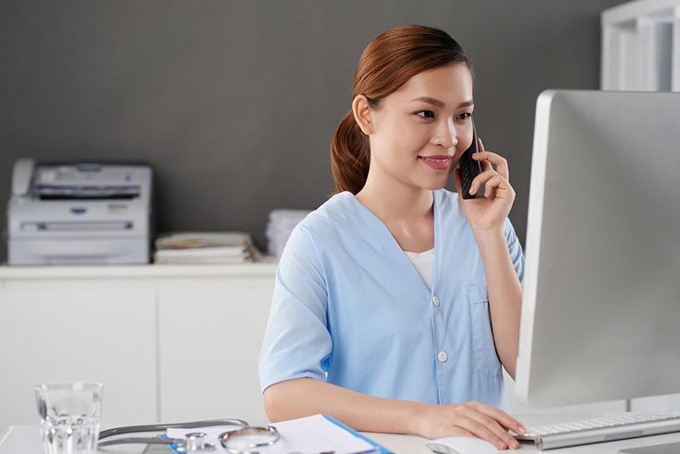 Nurse leader talking with a patient on the phone and using computer