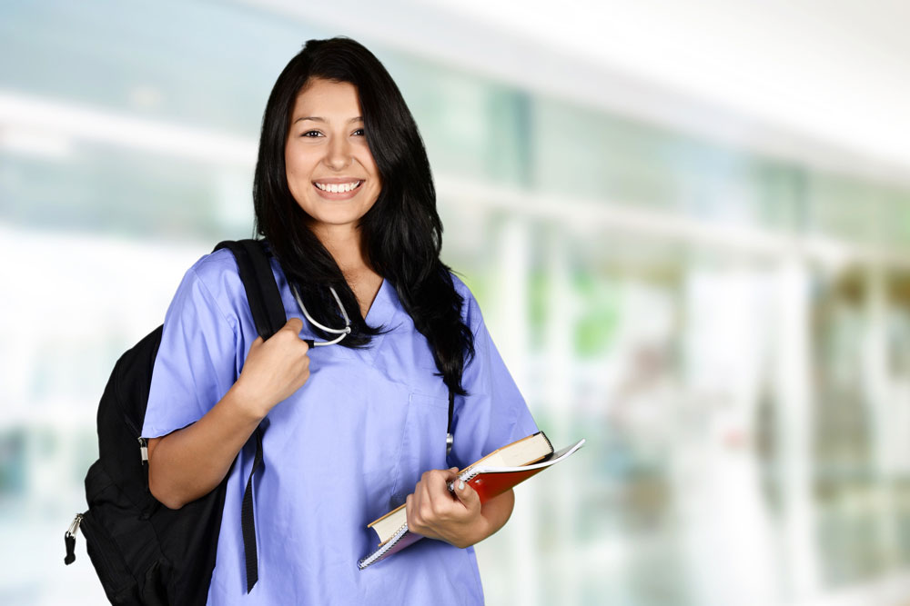 A practicing nurse holding a book and a notebook