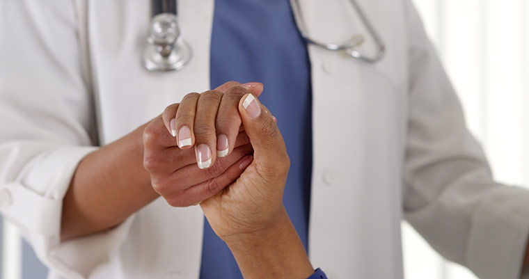 Close-up image of a nurse holding a patient's hand